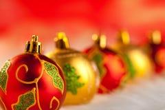 Χρυσά κόκκινα μπιχλιμπίδια Χριστουγέννων σε μια σειρά με τα φω'τα Στοκ εικόνες με δικαίωμα ελεύθερης χρήσης