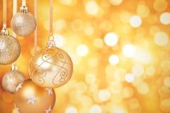 Χρυσά μπιχλιμπίδια Χριστουγέννων που κρεμούν μπροστά από ένα χρυσό υπόβαθρο Στοκ Εικόνες
