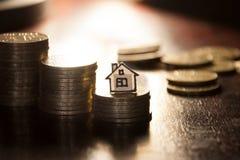 Χρυσά νομίσματα και σπίτι Στοκ φωτογραφία με δικαίωμα ελεύθερης χρήσης