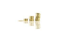 Χρυσά νομίσματα που συσσωρεύονται στο άσπρο υπόβαθρο με μια αντανάκλαση Στοκ Φωτογραφίες