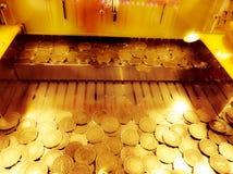 Χρυσά νομίσματα σε μια μηχανή μπουλντόζων νομισμάτων arcade Στοκ Εικόνες