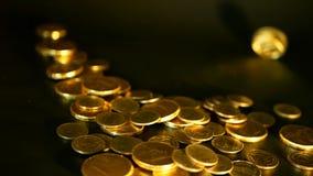 Χρυσά νομίσματα στο μαύρο υπόβαθρο Επιτυχία της επιχείρησης χρηματοδότησης, επένδυση, νομισματοποίηση των ιδεών, πλούτος, έννοια  φιλμ μικρού μήκους