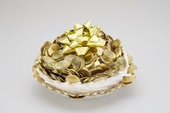 Χρυσά νομίσματα σωρών στο πλέγμα αφρού που τυλίγονται με τη χρυσή κορδέλλα Στοκ Φωτογραφία