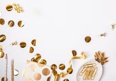 Χρυσά ντεκόρ και κομφετί χρώματος στο άσπρο υπόβαθρο στοκ φωτογραφίες