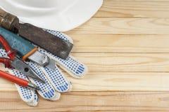 χρυσά πλήκτρα σπιτιών δάχτυλων κατασκευής έννοιας Εργαλεία κατασκευής, γάντια εργασίας και άσπρο κράνος στο ξύλινο υπόβαθρο Διάστ Στοκ Εικόνες