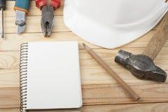 χρυσά πλήκτρα σπιτιών δάχτυλων κατασκευής έννοιας Εργαλεία εργασίας, άσπρο κράνος, σημειωματάριο και μολύβι στο ξύλινο υπόβαθρο Δ Στοκ φωτογραφία με δικαίωμα ελεύθερης χρήσης