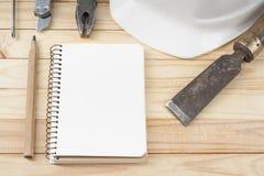 χρυσά πλήκτρα σπιτιών δάχτυλων κατασκευής έννοιας Εργαλεία εργασίας, άσπρο κράνος, σημειωματάριο και μολύβι στο ξύλινο υπόβαθρο Δ Στοκ Εικόνες