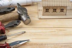χρυσά πλήκτρα σπιτιών δάχτυλων κατασκευής έννοιας Πρότυπα εργαλεία σπιτιών, σχεδίων και εργασίας στο ξύλινο υπόβαθρο Διάστημα αντ Στοκ φωτογραφία με δικαίωμα ελεύθερης χρήσης
