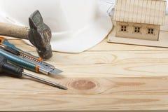 χρυσά πλήκτρα σπιτιών δάχτυλων κατασκευής έννοιας Πρότυπο σπίτι, εργαλεία εργασίας και άσπρο κράνος στο ξύλινο υπόβαθρο Διάστημα  Στοκ Φωτογραφία