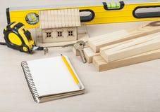 χρυσά πλήκτρα σπιτιών δάχτυλων κατασκευής έννοιας Πρότυπο σπίτι, εργαλεία εργασίας και σημειωματάριο με το μολύβι στον ξύλινο πίν Στοκ Φωτογραφία