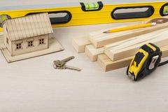 χρυσά πλήκτρα σπιτιών δάχτυλων κατασκευής έννοιας Πρότυπο σπίτι, εργαλεία εργασίας, κλειδιά Διάστημα αντιγράφων για το κείμενο Στοκ Φωτογραφίες