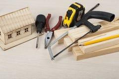 χρυσά πλήκτρα σπιτιών δάχτυλων κατασκευής έννοιας Πρότυπα σπίτι και εργαλεία στον ξύλινο πίνακα Διάστημα αντιγράφων για το κείμεν Στοκ Φωτογραφίες