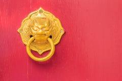 Χρυσά ρόπτρα πορτών με μορφή του λιονταριού με το δαχτυλίδι σε ένα κόκκινο ξύλο Στοκ Εικόνες