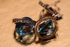 Χρυσά σκουλαρίκια με τα κρύσταλλα στο υπόβαθρο Στοκ Εικόνες