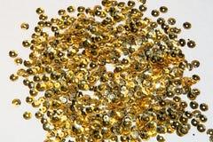 Χρυσά στρογγυλά τσέκια που ράβουν στο άσπρο υπόβαθρο Στοκ Φωτογραφία