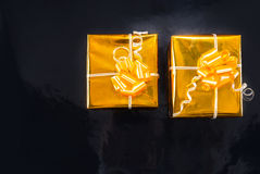 Χρυσά τυλιγμένα φύλλο αλουμινίου δώρα Χριστουγέννων στο Μαύρο στοκ εικόνα με δικαίωμα ελεύθερης χρήσης
