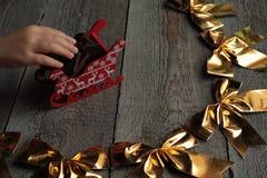 Χρυσά τόξα Χριστουγέννων στο ξύλινο υπόβαθρο το θαύμα θα αρχίσει σύντομα Στοκ Εικόνες