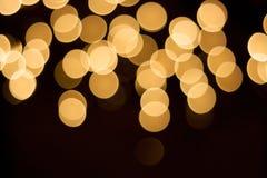 Χρυσά φω'τα bokeh της γιρλάντας Χριστουγέννων ανασκόπηση που θολώνεται Στοκ Εικόνες