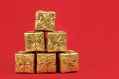 Χρυσά χριστουγεννιάτικα δώρα στην κόκκινη ανασκόπηση Στοκ Φωτογραφίες