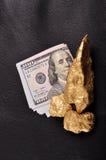 Χρυσά ψήγματα, δολάρια σε ένα μαύρο δέρμα υποβάθρου. Κινηματογράφηση σε πρώτο πλάνο. Στοκ Εικόνες