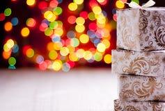 Χρυσά δώρα στο μουτζουρωμένο υπόβαθρο φω'των Στοκ Φωτογραφία