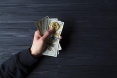 Χρυσά bitcoin και δολάρια στο αρσενικό χέρι σε ένα σκούρο μπλε ξύλινο υπόβαθρο Στοκ φωτογραφίες με δικαίωμα ελεύθερης χρήσης