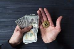 Χρυσά bitcoin και δολάρια στο αρσενικό χέρι σε ένα σκούρο μπλε ξύλινο υπόβαθρο Στοκ Εικόνες