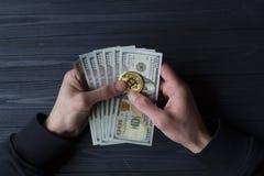Χρυσά bitcoin και δολάρια στο αρσενικό χέρι σε ένα σκούρο μπλε ξύλινο υπόβαθρο Στοκ Φωτογραφία