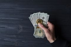 Χρυσά bitcoin και δολάρια στο αρσενικό χέρι σε ένα σκούρο μπλε ξύλινο υπόβαθρο Στοκ εικόνα με δικαίωμα ελεύθερης χρήσης