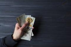 Χρυσά bitcoin και δολάρια στο αρσενικό χέρι σε ένα σκούρο μπλε ξύλινο υπόβαθρο Στοκ Εικόνα