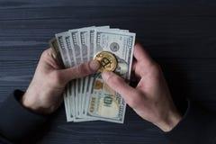Χρυσά bitcoin και δολάρια στο αρσενικό χέρι σε ένα σκούρο μπλε ξύλινο υπόβαθρο Στοκ εικόνες με δικαίωμα ελεύθερης χρήσης