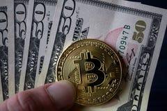 Χρυσά bitcoin και δολάρια στο αρσενικό χέρι σε ένα σκούρο μπλε ξύλινο υπόβαθρο Στοκ Φωτογραφίες