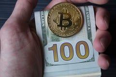 Χρυσά bitcoin και δολάρια στο αρσενικό χέρι σε ένα σκούρο μπλε ξύλινο υπόβαθρο Στοκ φωτογραφία με δικαίωμα ελεύθερης χρήσης