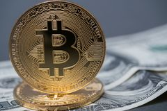 Χρυσά bitcoins στο υπόβαθρο των λογαριασμών 100 δολαρίων Στοκ Φωτογραφία