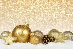 Χρυσές διακοσμήσεις Χριστουγέννων με το αστράφτοντας υπόβαθρο Στοκ Εικόνες