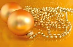 Χρυσές διακοσμήσεις Χριστουγέννων στο χρυσό υπόβαθρο Στοκ Φωτογραφία