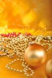Χρυσές διακοσμήσεις Χριστουγέννων στο χρυσό υπόβαθρο Στοκ Εικόνες