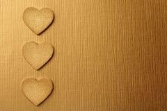 Χρυσές καρδιές σε ένα χρυσό υπόβαθρο στοκ φωτογραφίες