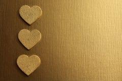 Χρυσές καρδιές σε ένα χρυσό υπόβαθρο στοκ εικόνες
