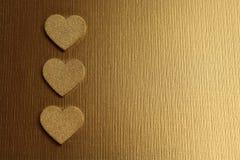 Χρυσές καρδιές σε ένα χρυσό υπόβαθρο στοκ φωτογραφία με δικαίωμα ελεύθερης χρήσης