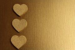 Χρυσές καρδιές σε ένα χρυσό υπόβαθρο στοκ εικόνα