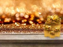 Χρυσές κιβώτια και κορδέλλα δώρων στον ξύλινο πίνακα, bokeh υπόβαθρο Στοκ Φωτογραφίες
