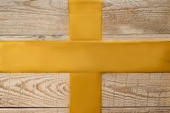 Χρυσές κορδέλλες που διασχίζονται στο σαφές ξύλινο υπόβαθρο Στοκ φωτογραφία με δικαίωμα ελεύθερης χρήσης
