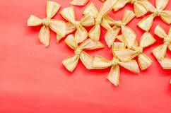 Χρυσές κορδέλλες τόξων σε κόκκινο χαρτί Στοκ Εικόνες