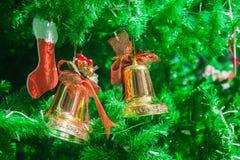 Χρυσές κουδούνια και διακόσμηση καλτσών στο χριστουγεννιάτικο δέντρο Στοκ Φωτογραφία
