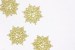 Χρυσές νιφάδες χιονιού με το ακτινοβολώντας άσπρο υπόβαθρο όπως η ανασκόπηση είναι μπορεί θέμα απεικόνισης Χριστουγέννων χρησιμοπ στοκ εικόνα