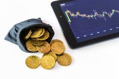 Χρυσές νομίσματα και ταμπλέτα που τοποθετούνται σε έναν άσπρο πίνακα που παρουσιάζει μια γραφική παράσταση Στοκ φωτογραφία με δικαίωμα ελεύθερης χρήσης