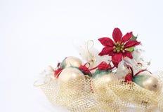 Χρυσές σφαίρες Χριστουγέννων και κόκκινο puansetii Στοκ Φωτογραφία