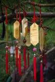 Χρυσές ταοϊστικές γοητείες προσευχής που κρεμούν από ένα δέντρο Στοκ Φωτογραφίες