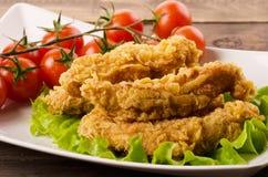 Χρυσές τηγανισμένες λουρίδες κοτόπουλου στο πασπάλισμα με ψίχουλα στοκ εικόνα